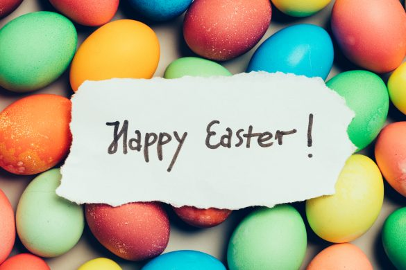 """Happy Easter"" written on a piece of white paper. Colorful eggs. Holiday wishes."
