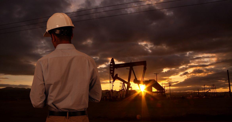 Engineer wearing hard hat helmet checking oil derrick field