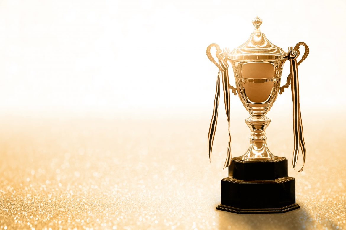 Gold Trophy competition on the abstract glitter background with copy space