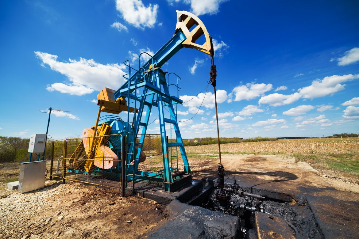 Landscape with oil pump under blue sky with clouds in a sunny day